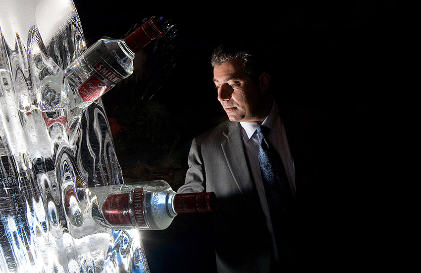 "alt=""Diner standing behind a vodka ice sculpture at a corporate buffet"""
