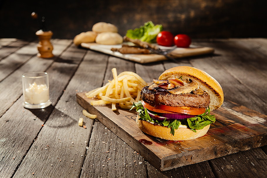 A beef hamburger/burger with fries sitting on a table ready to eat - Photographed by Gold Coast/Brisbane food photographer, Paul Williams