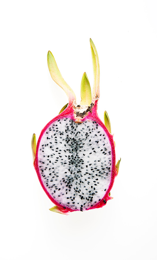 A white Dragonfruit cross section showing the seeds and beautiful colours.