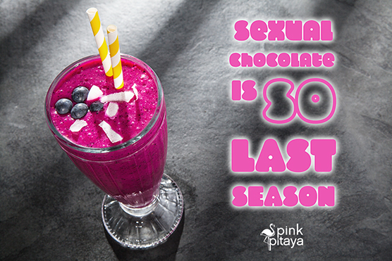 A glass of fruit smoothie made from Pink Pitaya (Dragonfruit), topped with blueberries and coconut.