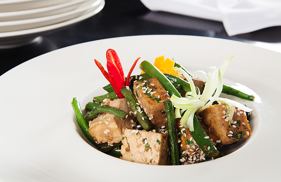 A_fine_dining_vegan_dish_of_tofu_beans_carrots_onion_sesame_seeds_chilli_served_in_a_white_bowl