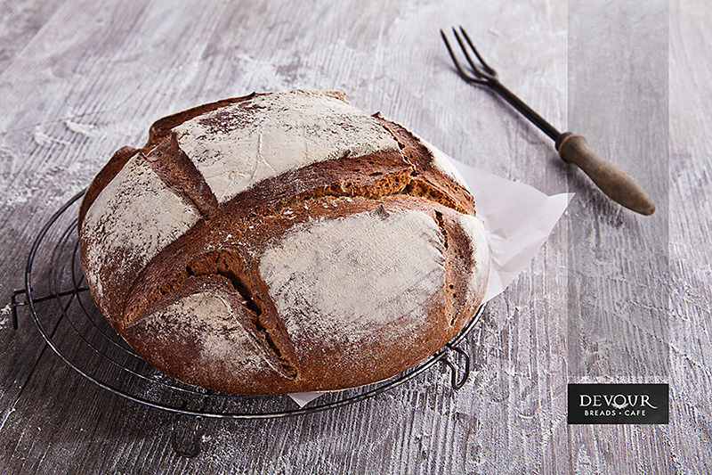 An image of a round loaf of artisanal crusty bread with a rustic serving fork in the background, on a timber tabletop, surrounded by scattered flour.