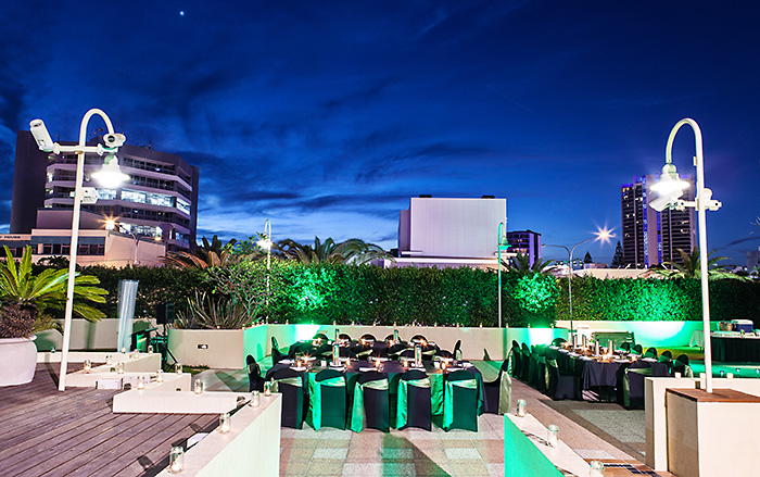 WIde angle shot of a candlelit outdoor event venue at night with set tables.