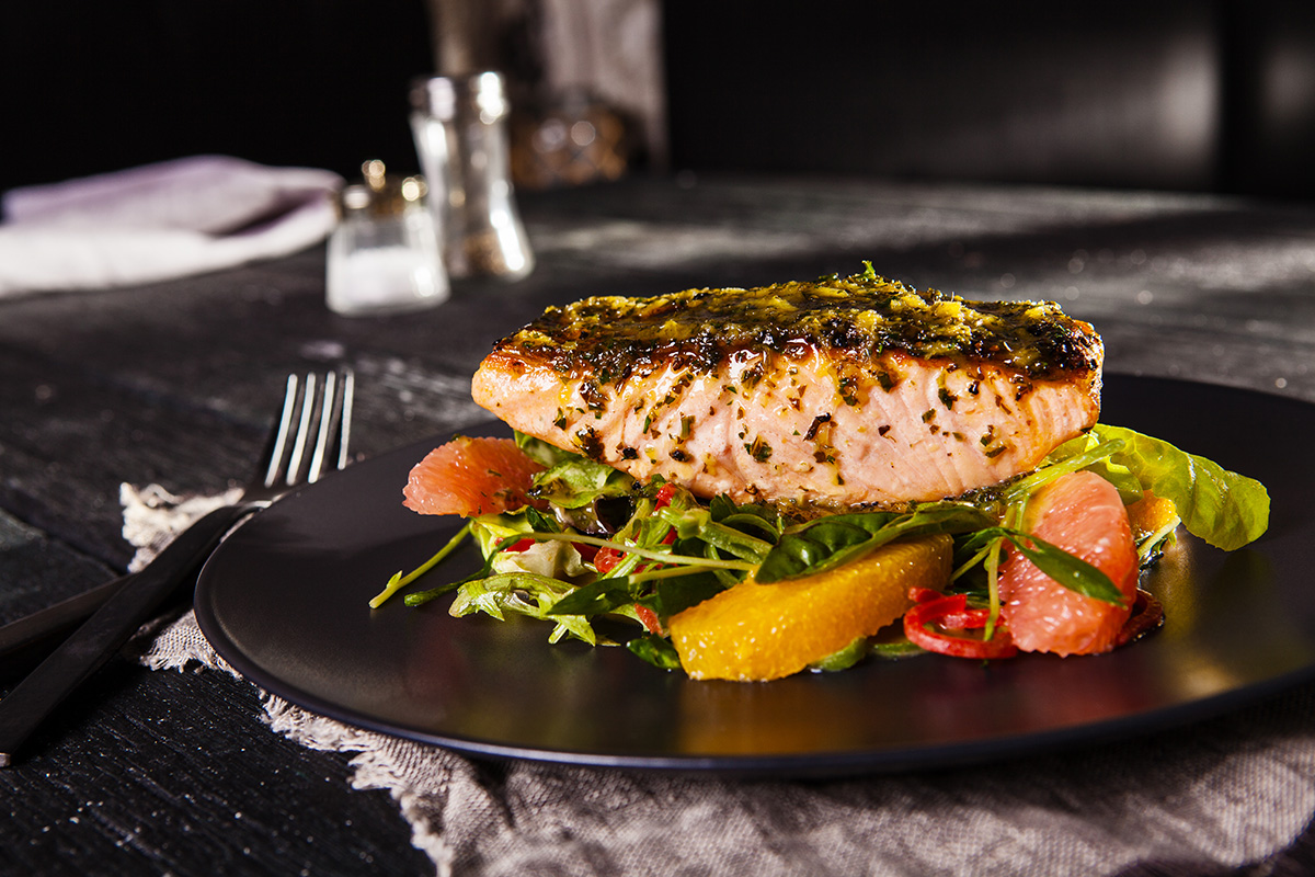 An image of a cooked salmon fillet on a black rustic timber restaurant table