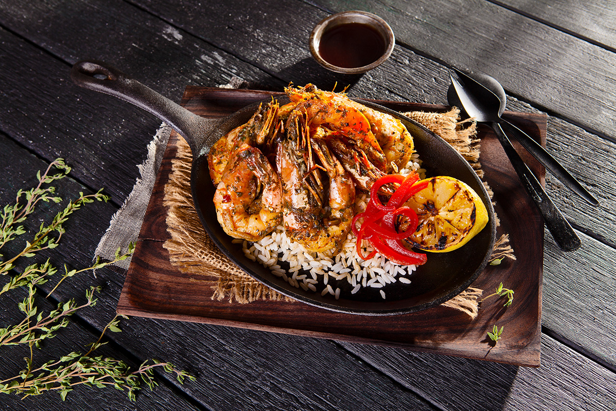 An image of a cooked King Prawns served onto a black rustic timber restaurant table