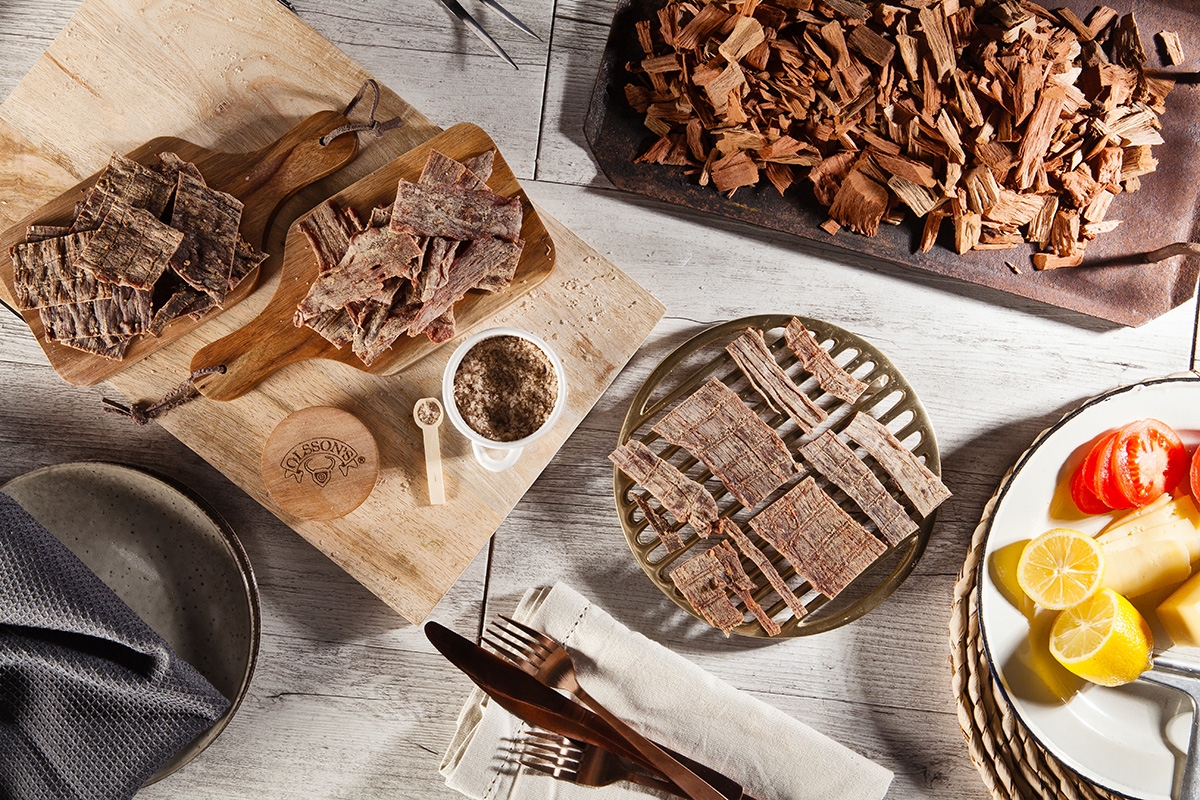 Top-down image of beef jerky, surrounded by complimentary foods on a table to share